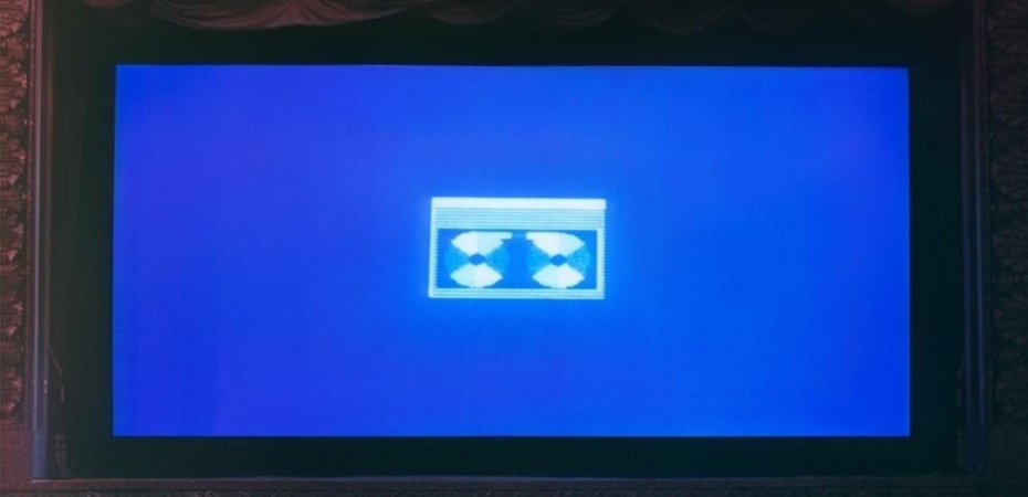 A cinema screen displaying a grainy VHS tape icon on a blue background